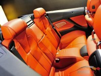 Rear seats with orange leather upholstery in a BMW M6